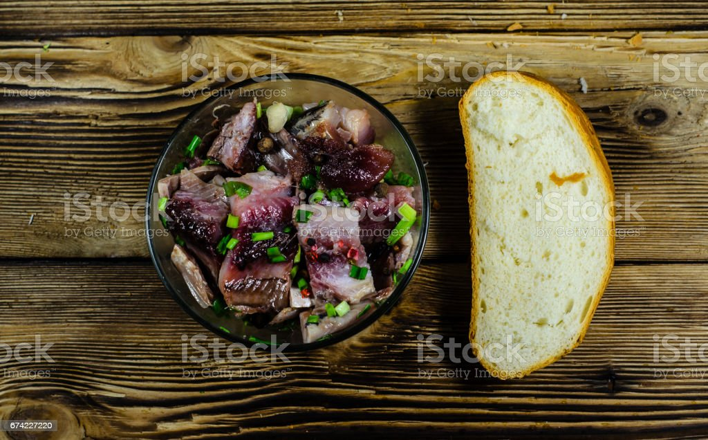 Herring with spices in glass bowl and sliced bread on wooden table. Top view stock photo