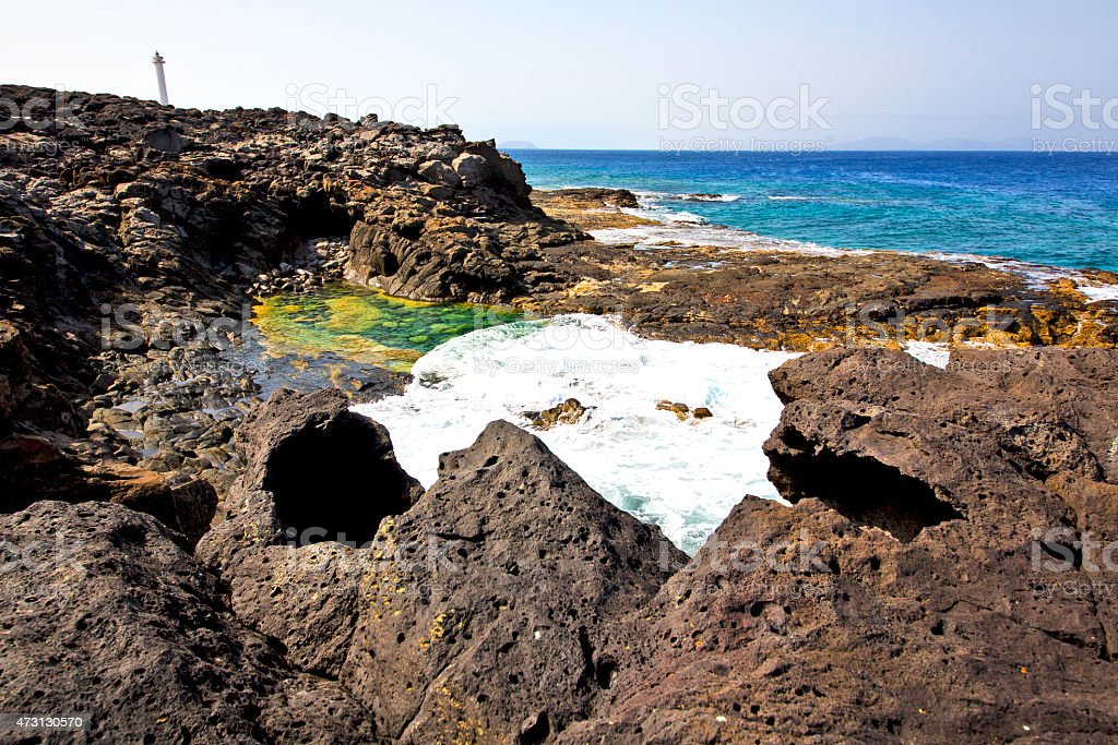 hervideros brown rock in white coast lighthouse stock photo