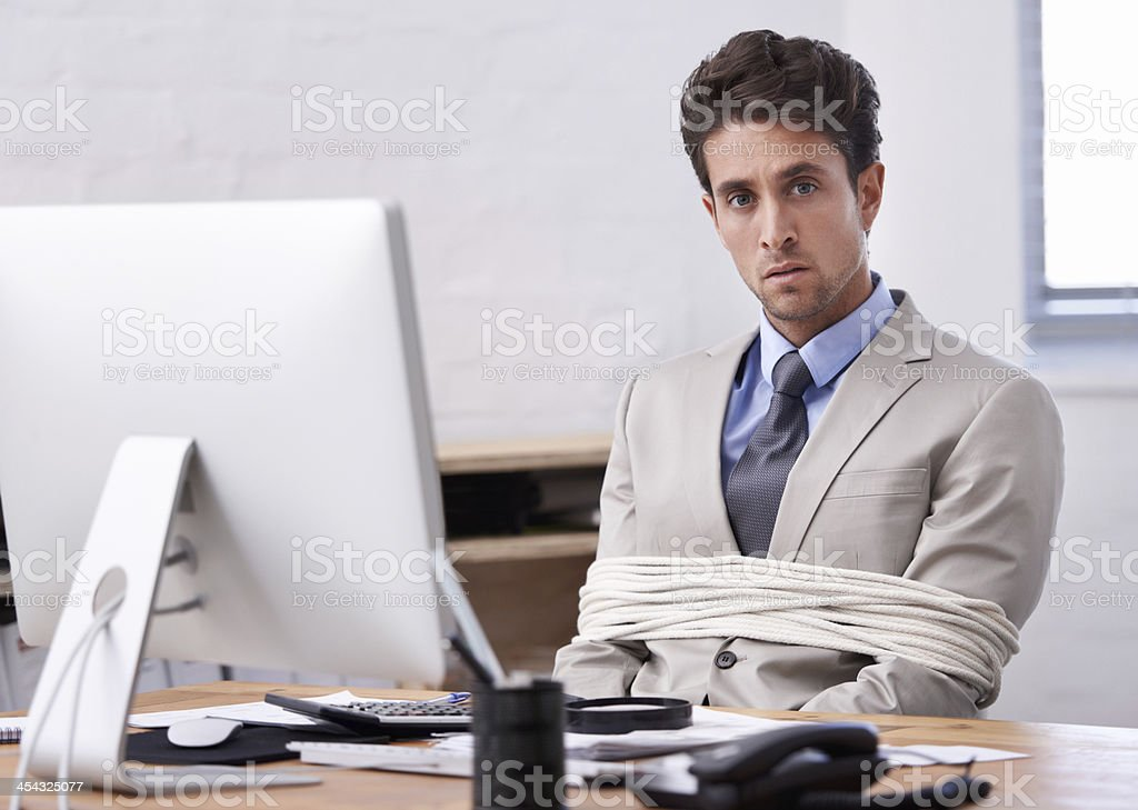 He's always stuck to his desk stock photo