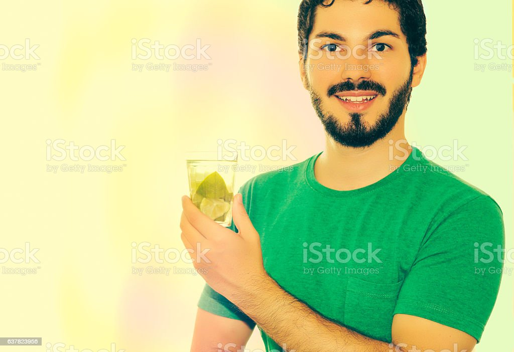 He's showing a glass with a drink made of lemon. stock photo