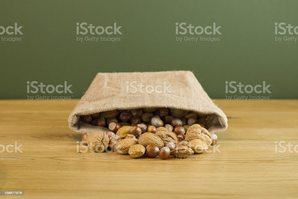 Hessian sack with mixed nuts spilling out royalty-free stock photo
