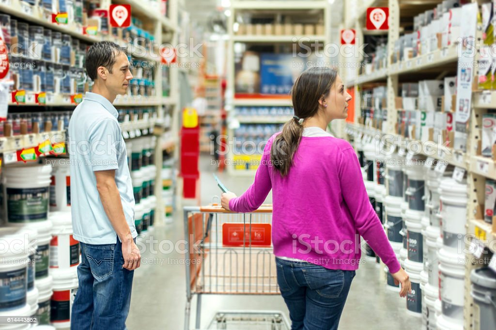 Heterosexual couple choosing a paint type stock photo