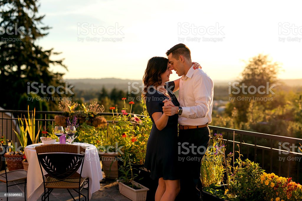 Heterosexual couple dancing after a romantic dinner on a veranda deck...