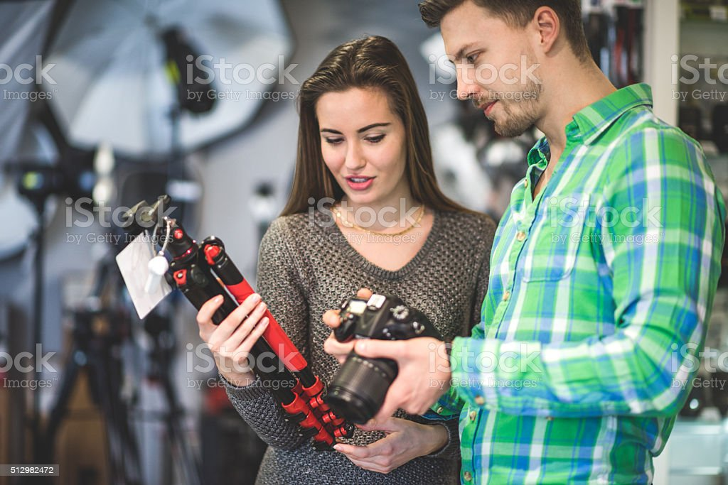 Heterosexual couple examining photographic equipment stock photo