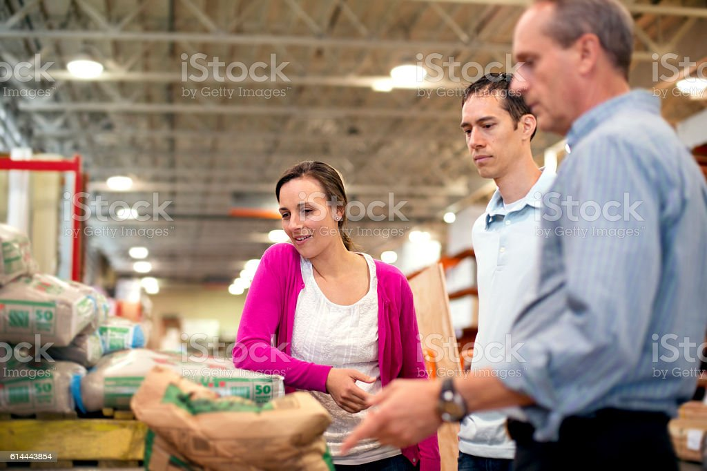 Heterosexual couple getting advice from a hardware store employee stock photo