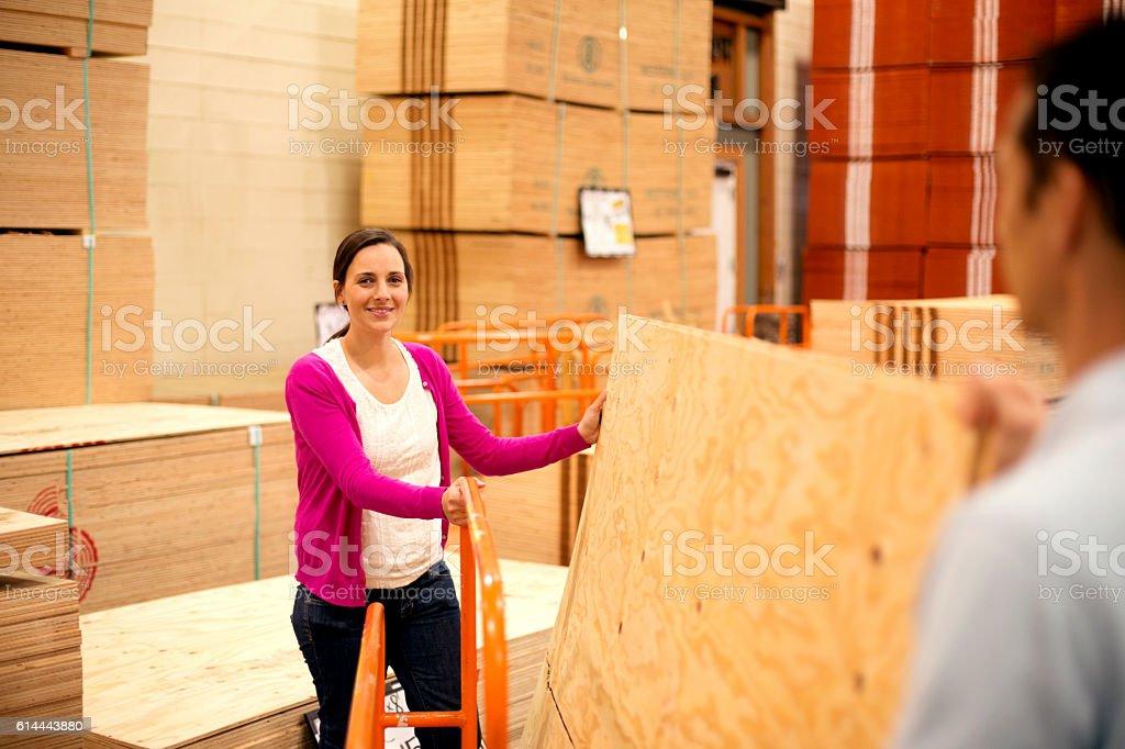 Heterosexual couple lifting plywood boards stock photo