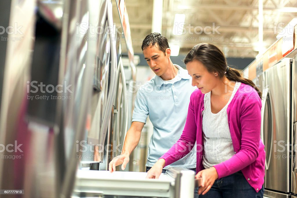 Heterosexual couple looking at the features of a refrigerator stock photo