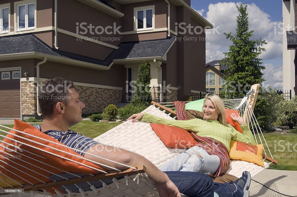 Heterosexual couple relaxing in front of their new suburban hous royalty-free stock photo