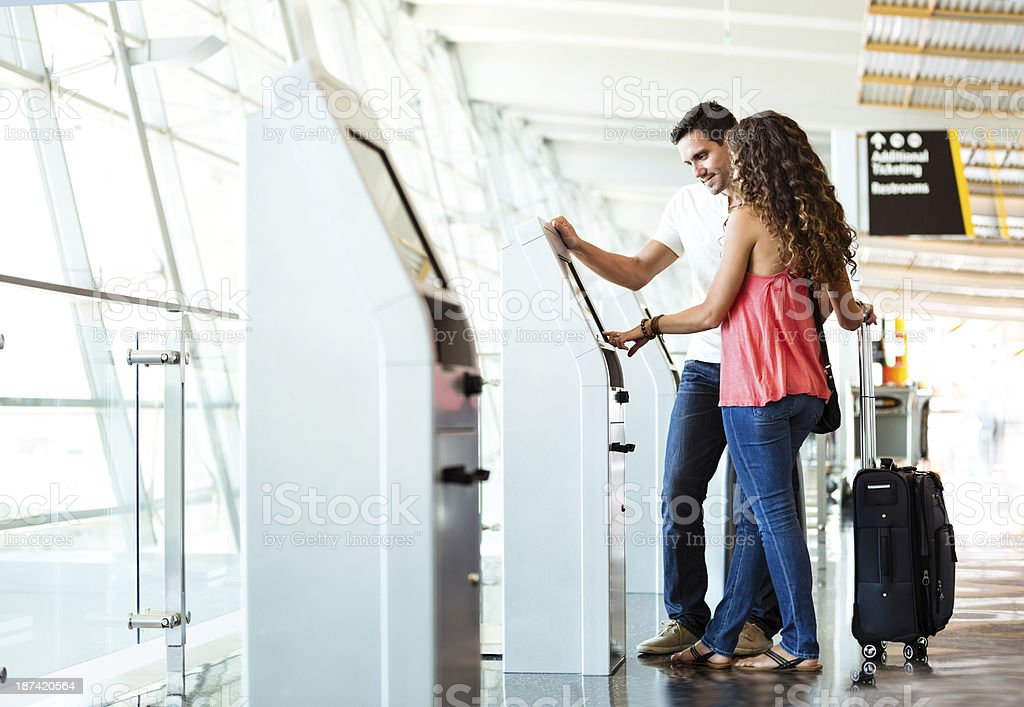 Heterosexual Couple Using Quick Check-In At Airport royalty-free stock photo