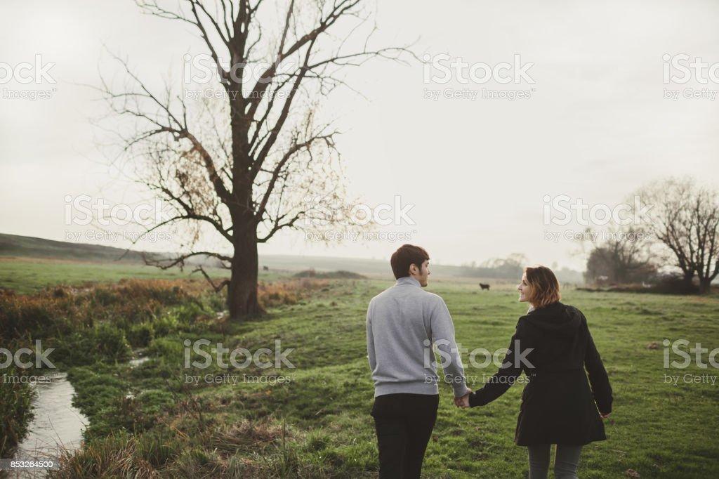 Young Caucasian heterosexual couple walking on the field