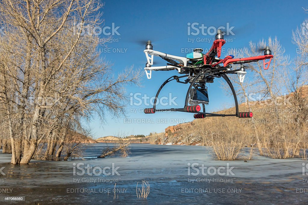 hexacopter drone flying over lake stock photo