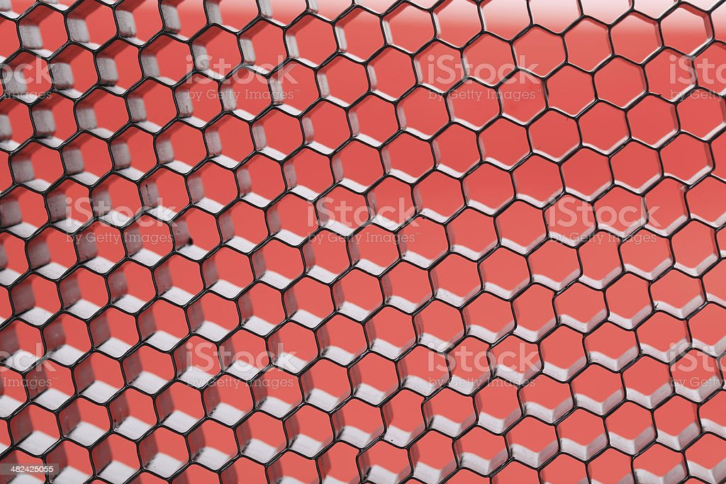 Hexagonal mesh on a red background. royalty-free stock photo