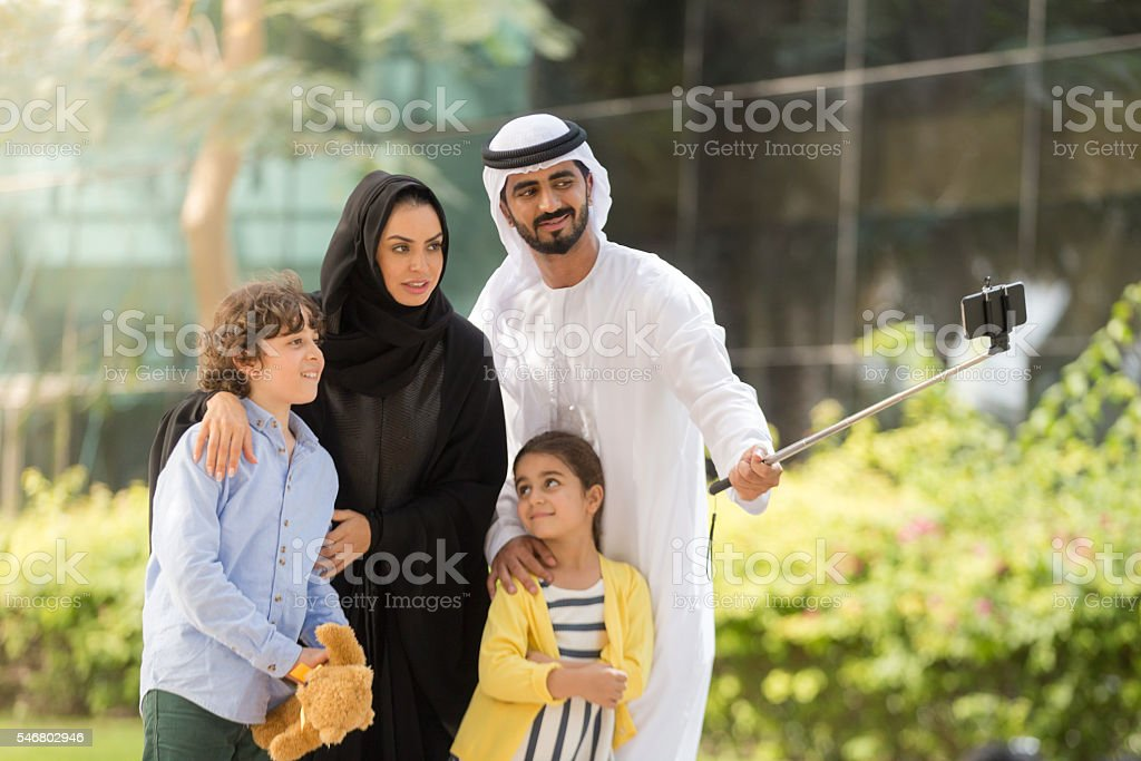 Hey, everyone look at the camera for a family selfie. stock photo