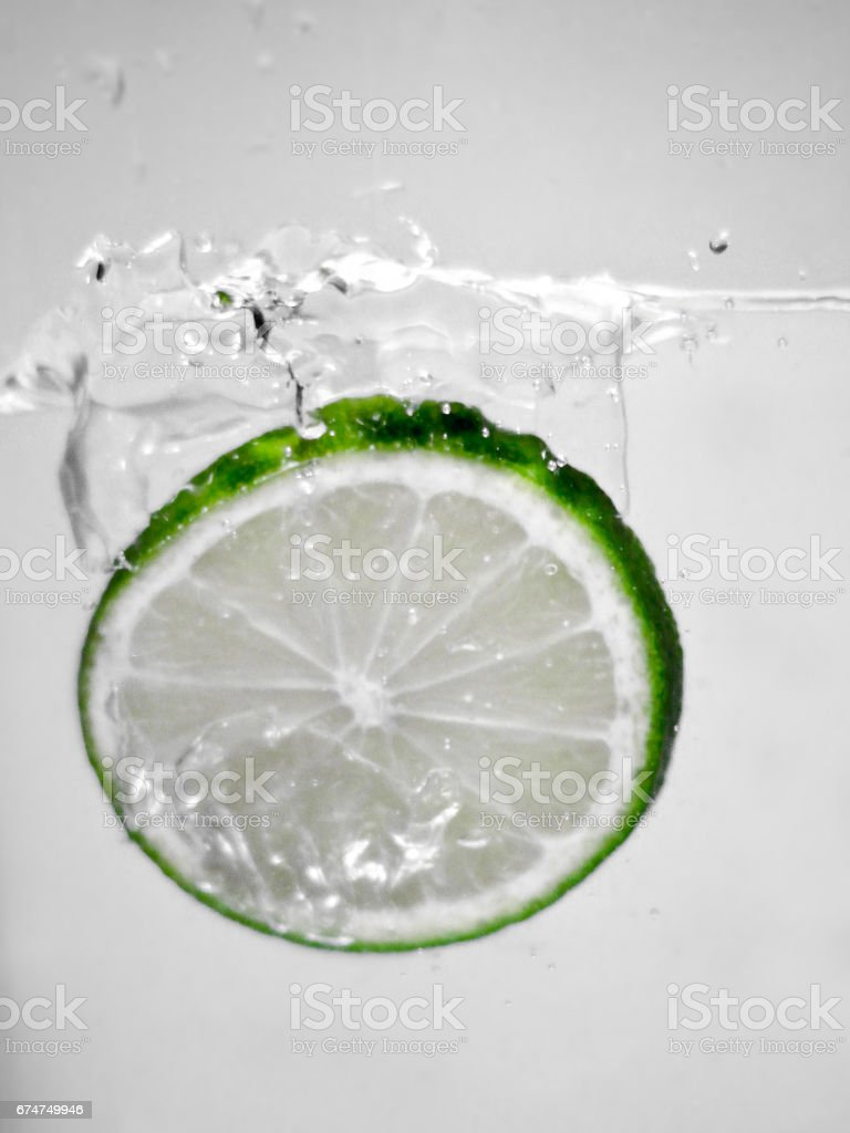 Hey fresh and cool lime fruites jumping in cold water. stock photo