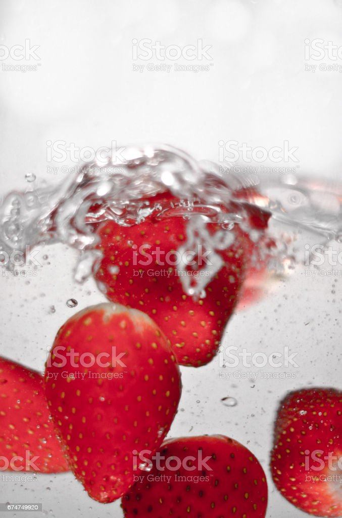 Hey fresh and cool strawberries jumping in cold water. stock photo