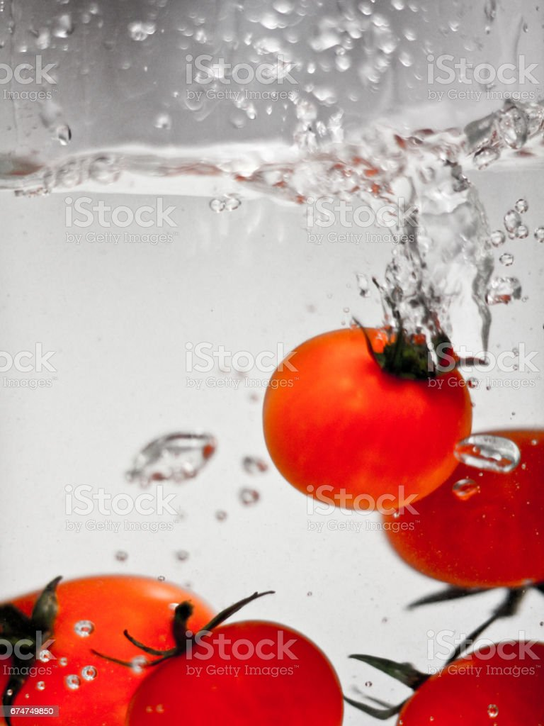Hey fresh and cool tomatos jumping in cold water. stock photo