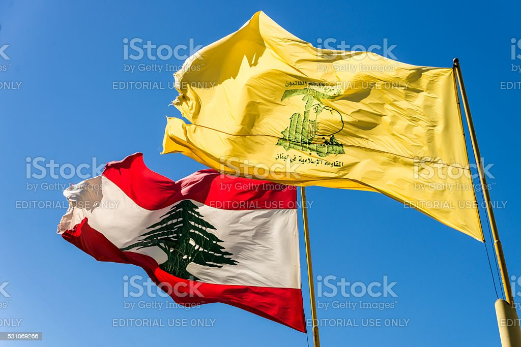 Hezbollah and Lebanese flags fly side by side stock photo