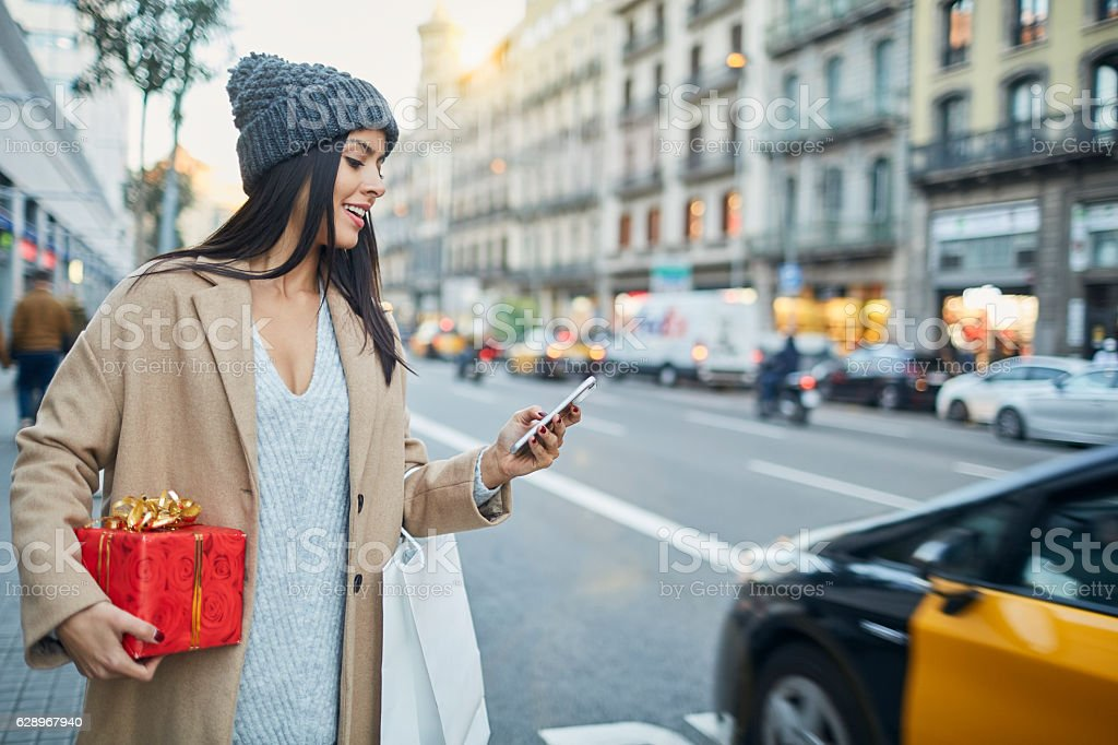 Hialing a taxi with smart phone app. Christmas shopping. stock photo