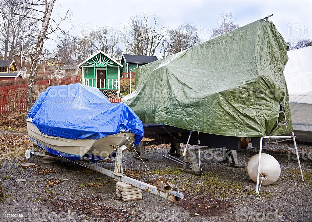 Hibernating boats on lnd covered with tarpaulins. Stockholm, Sweden stock photo