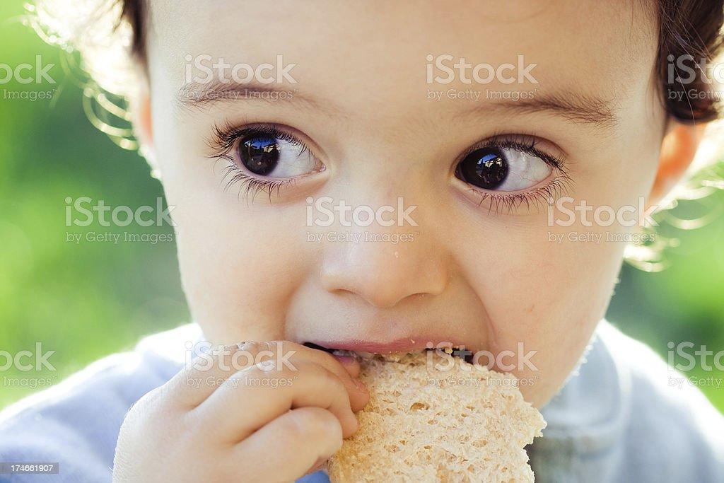 hidden kid devouring bread stock photo