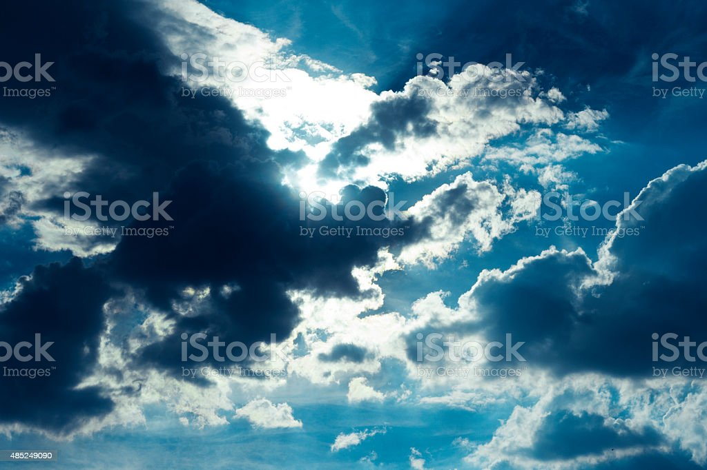Hidden sun behind clouds in the sky stock photo
