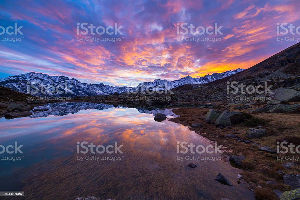 High altitude alpine lake, reflections at sunset stock photo