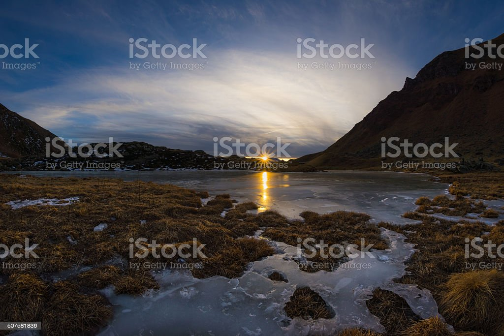 High altitude frozen alpine lake, fisheye view at sunset stock photo