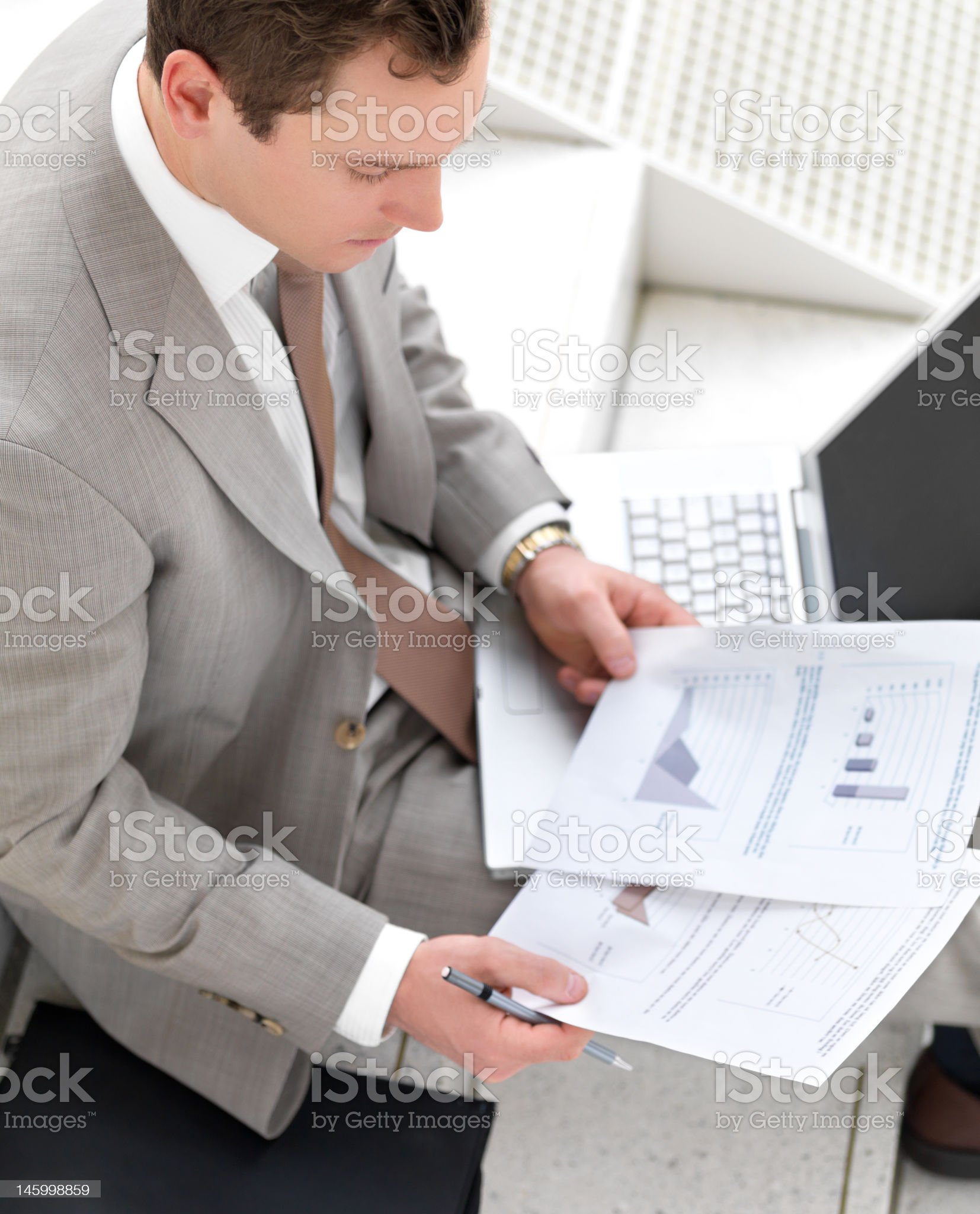High angle businessman sitting with documents and laptop royalty-free stock photo