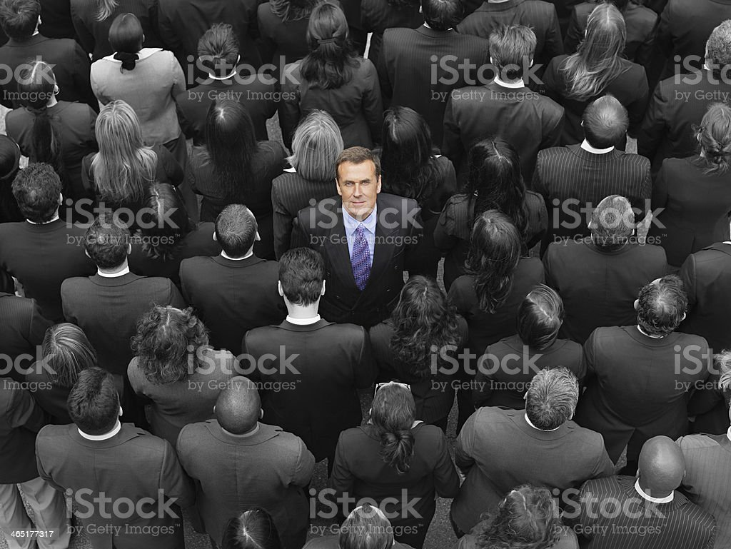 High angle view of a businessman standing amidst businesspeople stock photo
