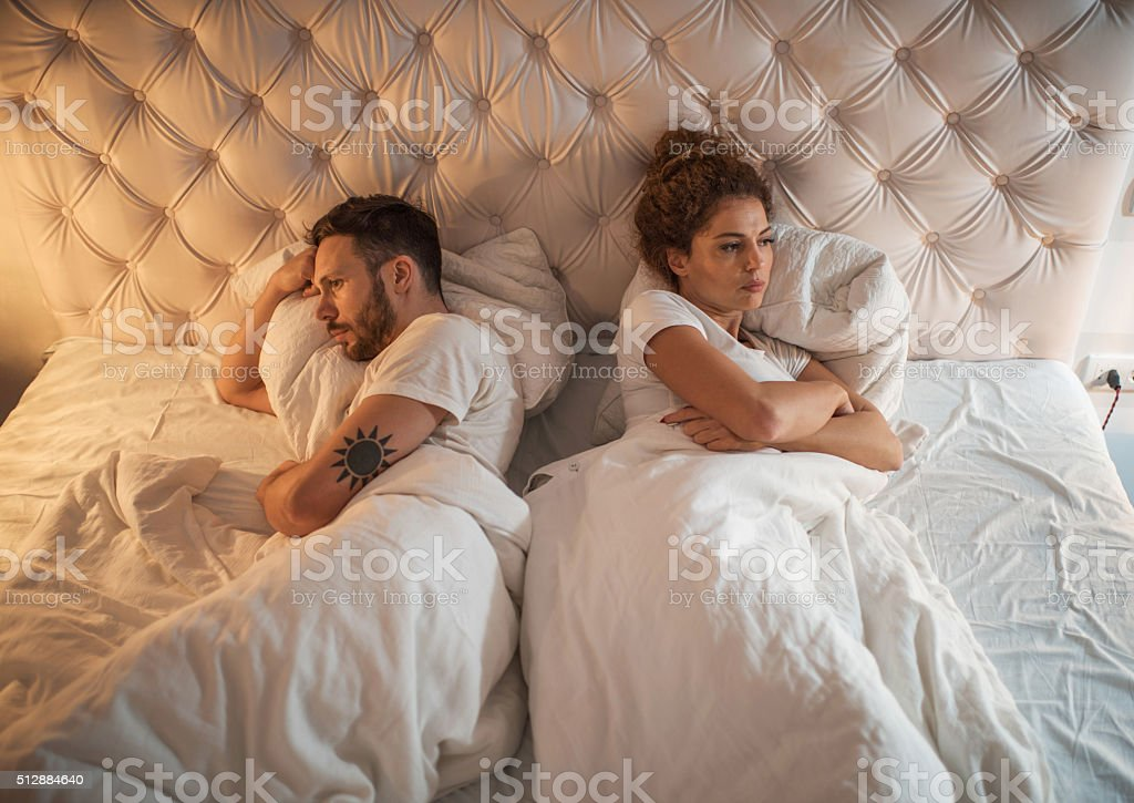 High angle view of a displeased couple in bed. stock photo