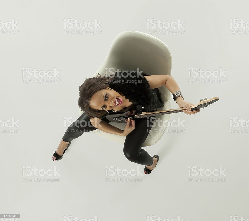 High angle view of a woman playing guitar on chair royalty-free stock photo