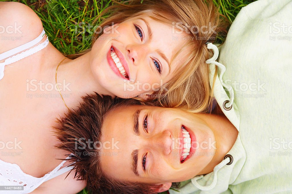High angle view of a young couple lying on grass royalty-free stock photo
