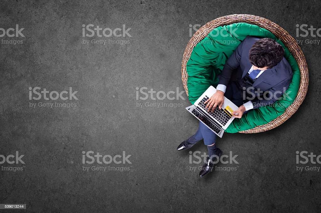 High angle view of a young man doing online shopping stock photo