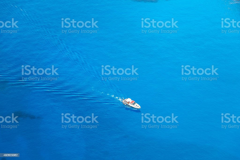 high angle view of boat with wake in blue sea stock photo