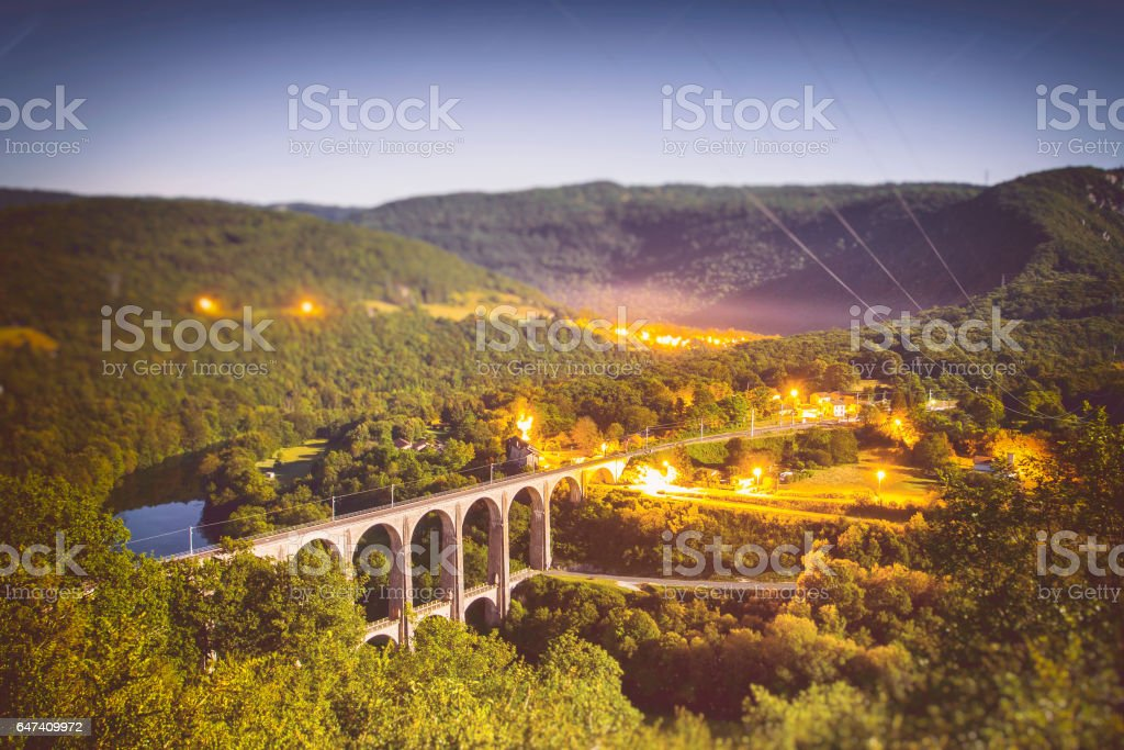 High angle view of french Bugey mountains beginning of Jura landscape by summer night with old stone railway viaduct arch bridge crossing Ain river under moonlight stock photo