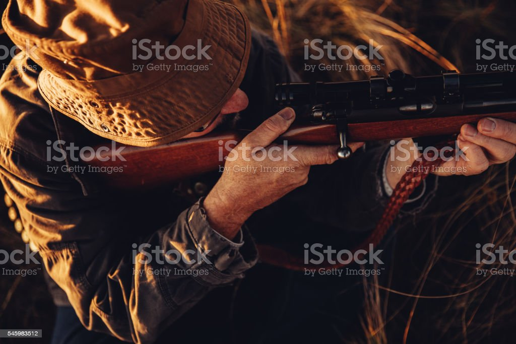 High angle view of hunter loading his rifle to shoot stock photo