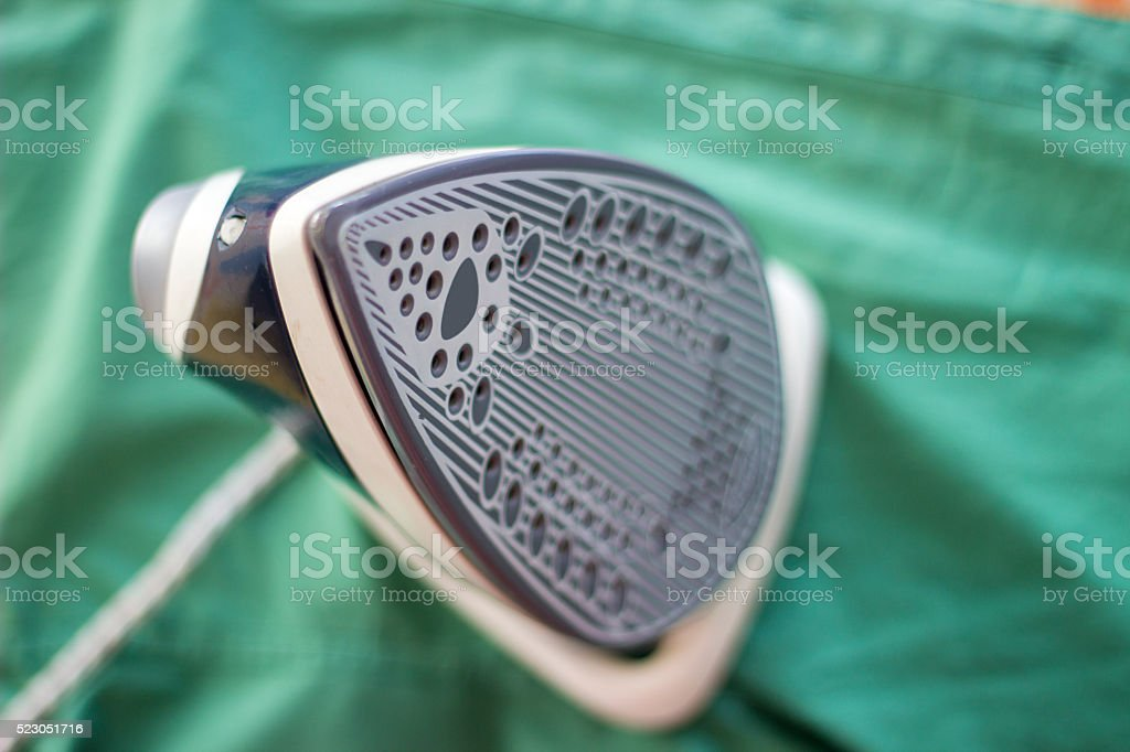High angle view of iron over green shirt stock photo