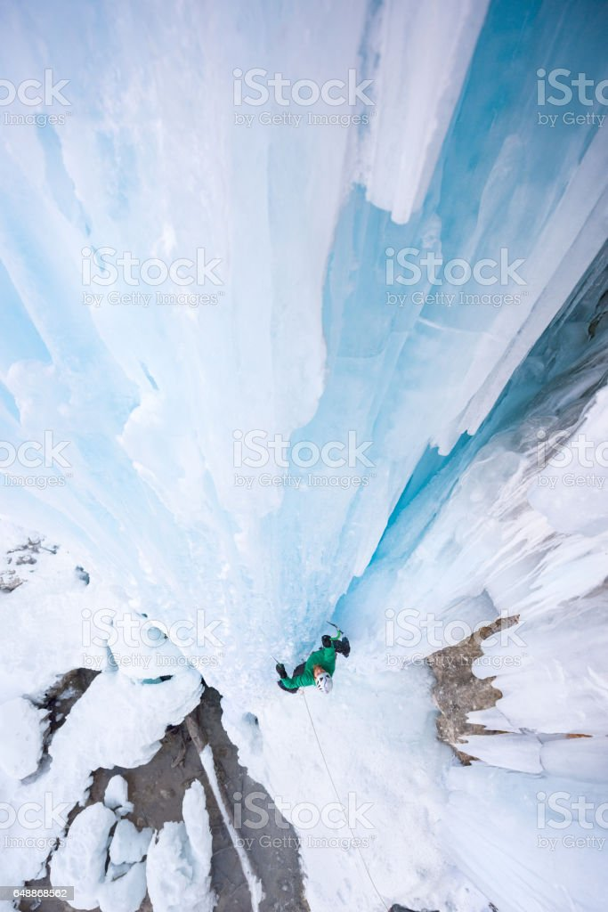 High angle view of man ice climbing on forzen waterfall stock photo