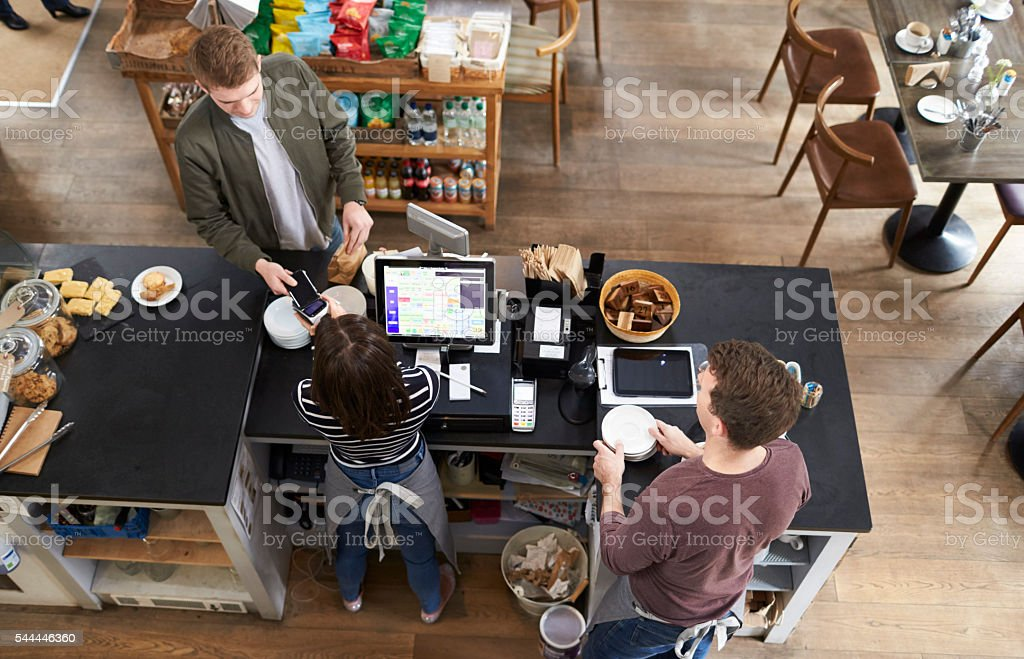 High angle view of man paying over counter at a coffee stock photo