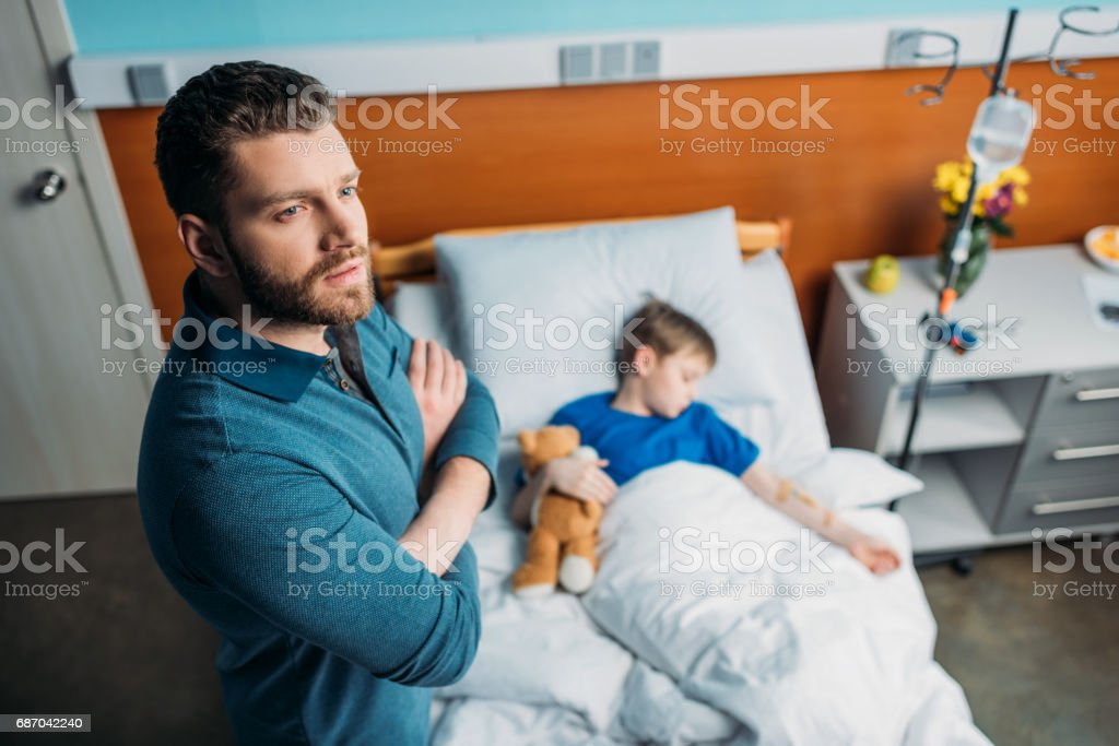 high angle view of pensive dad standing near sick son in hospital bed stock photo
