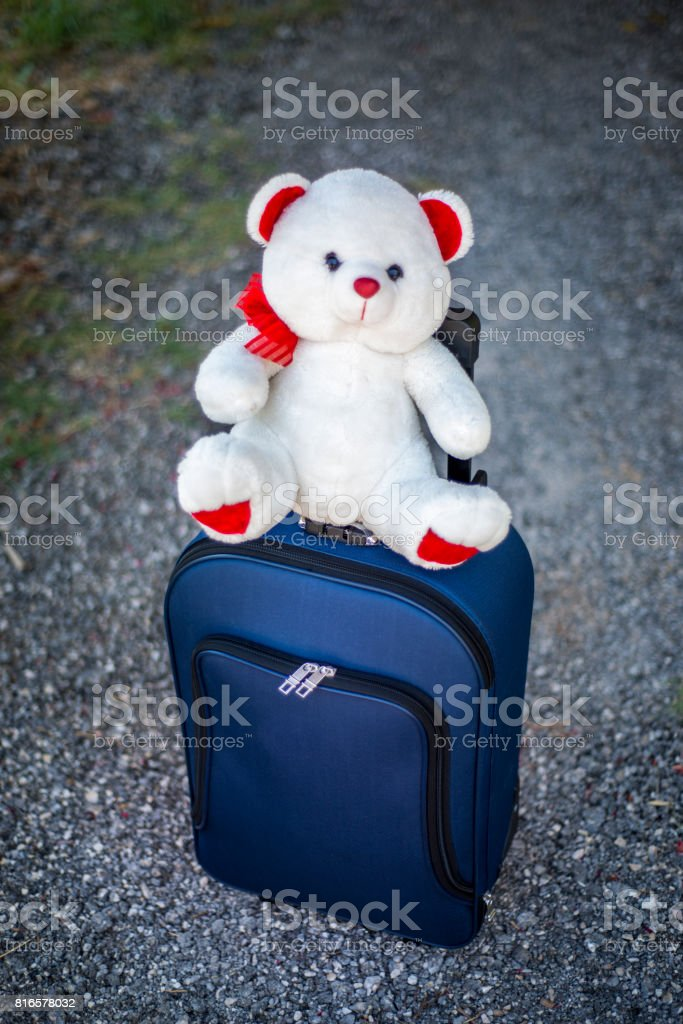 High angle view of single suitcase on floor with bear toy. Horizontal...