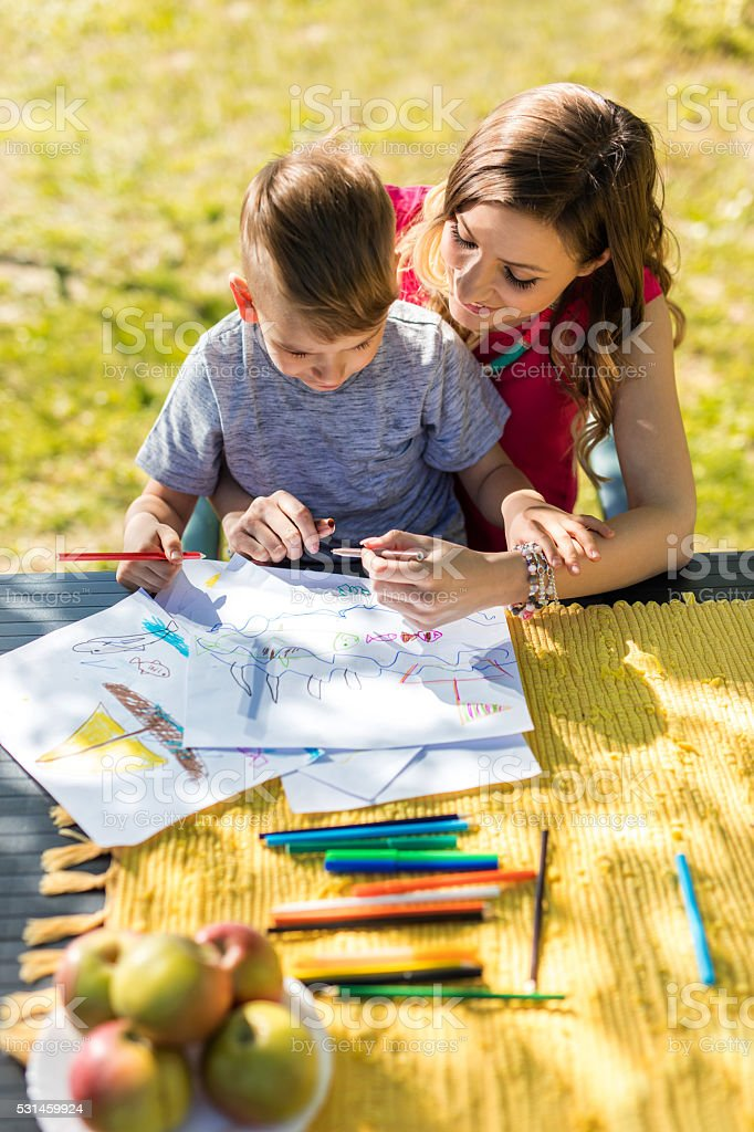 High angle view of smiling mother and son drawing outdoors. stock photo