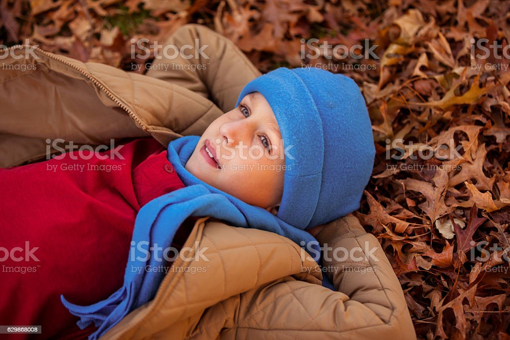 High angle view of thoughtful boy lying at park during stock photo