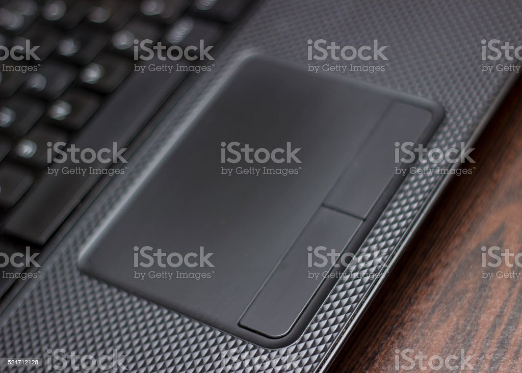 High angle view of touchpad of laptop over wooden background stock photo