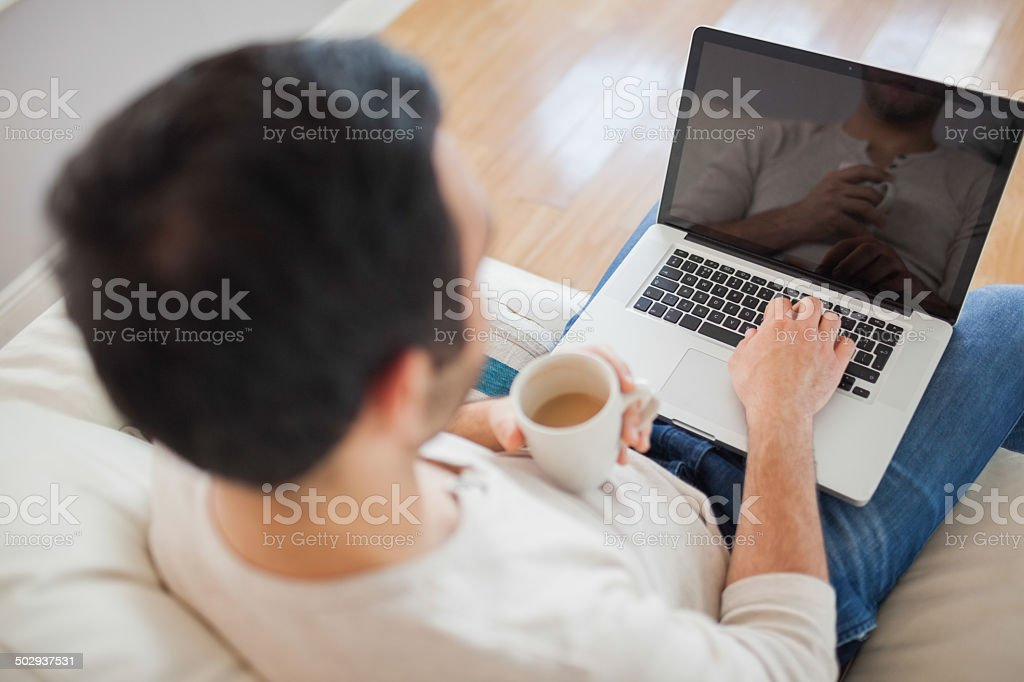 High angle view of young man using his laptop stock photo