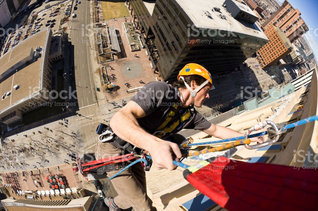 High Angle Worker Dangling From Tall Building stock photo