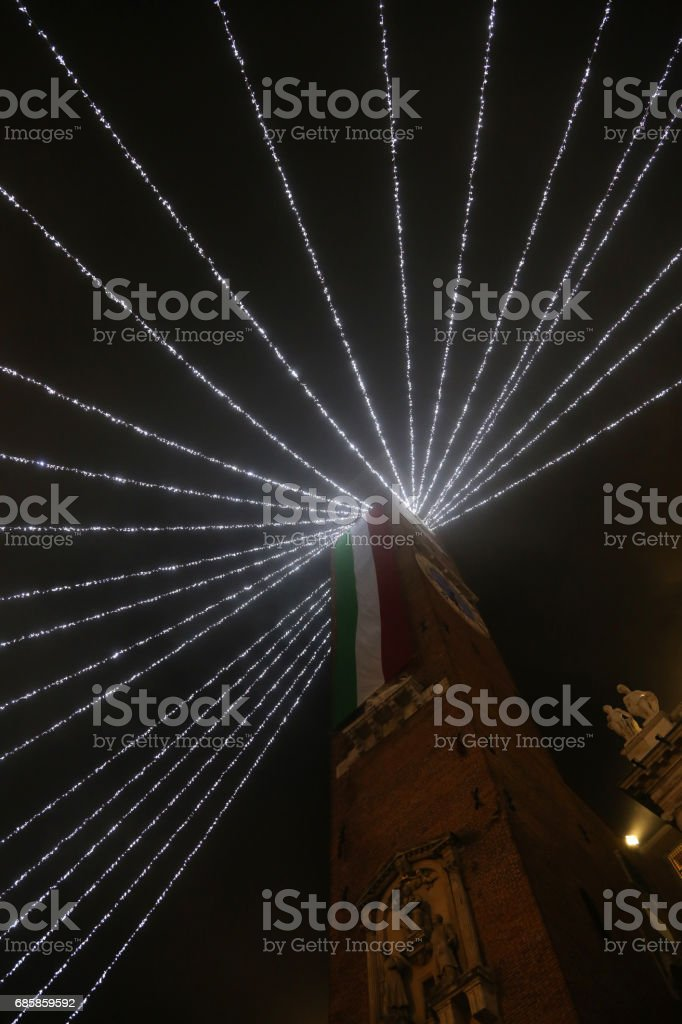 High bell tower with huge Italian flag with Christmas lights in the city of Vicenza in Italy stock photo