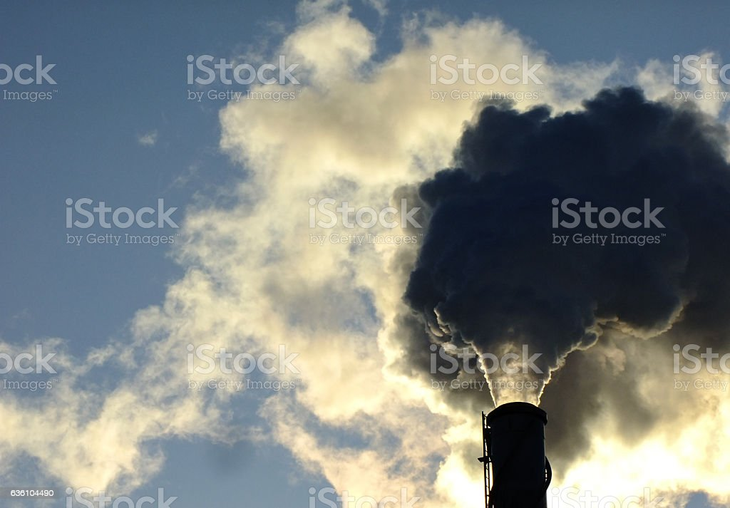 High Chimney emits Smoke during Sunset stock photo
