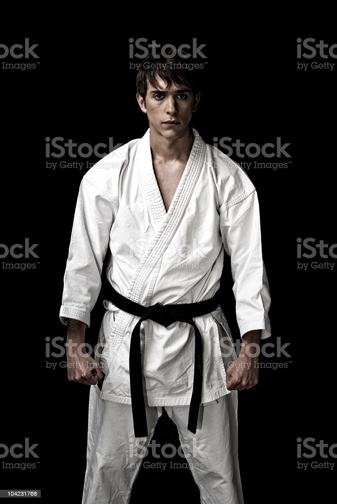 High Contrast karate male fighter on black background. stock photo