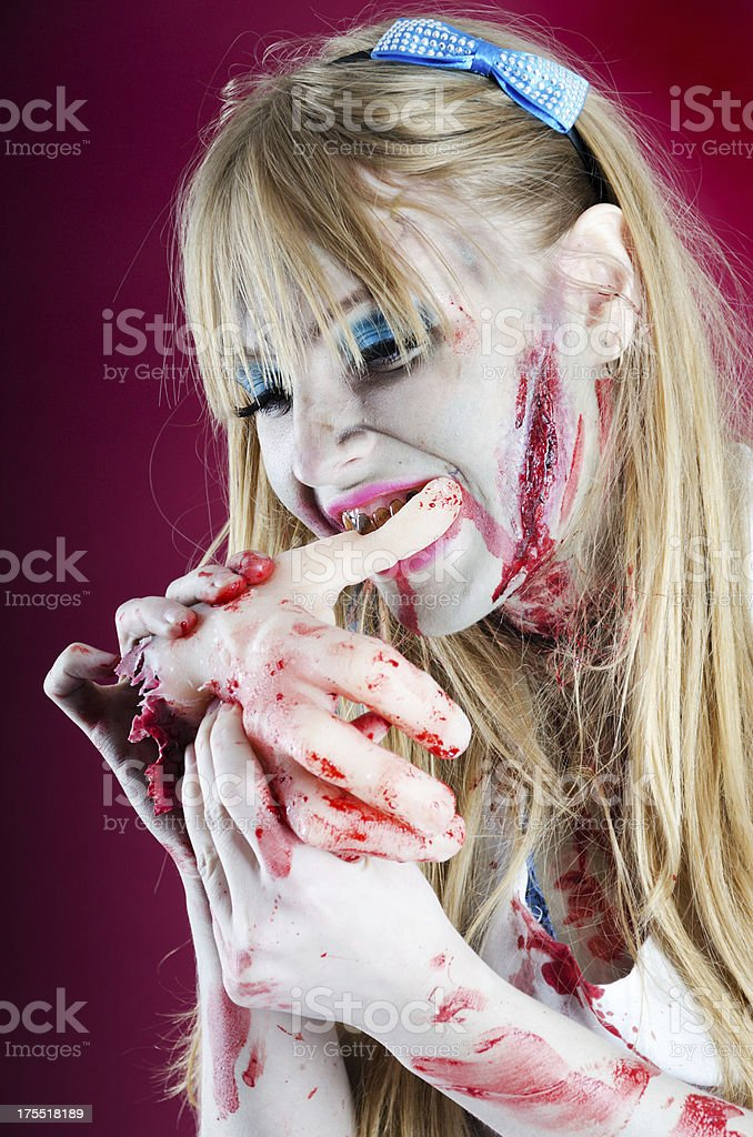 High contrast vertical of Zombie Alice eating hand. stock photo